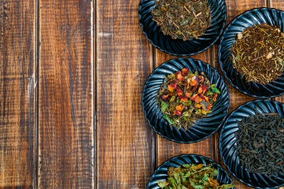 Different kinds of tea on plates on wooden background