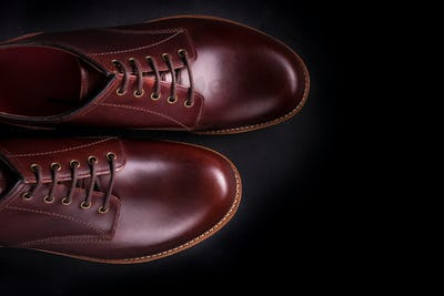 Brown oxford shoes on black background. Top view. Copy space.