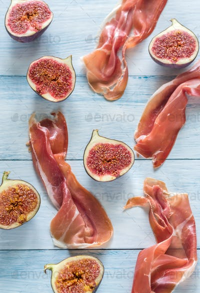 Slices of jamon with figs on the wooden background