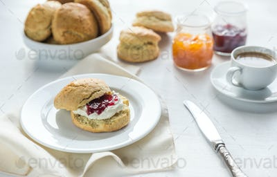 Scones with cream and fruit jam and cup of coffee