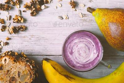 Berry farm yogurt in a jar, granola, banana, bread loaf