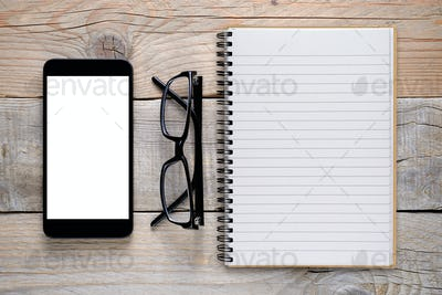 Smartphone, glasses and notepad on wooden table top view