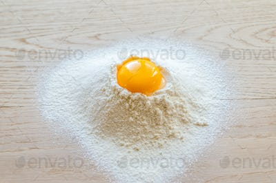 Broken egg in flour