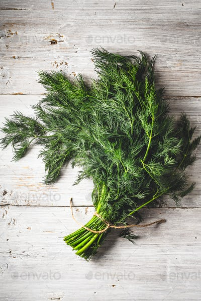 Bunch of dill on the white wooden table vertical