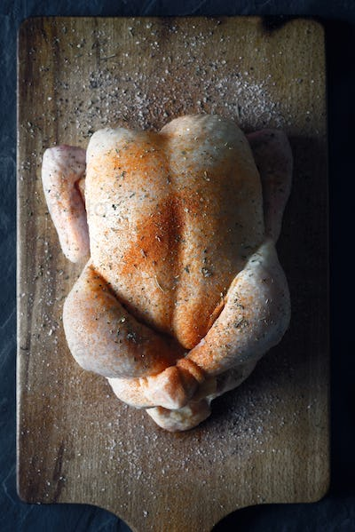 Raw Thanksgiving day turkey with spices on the wooden board top view