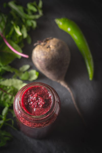 Vegetable smoothie with blurred ingredients on the dark stone background vertical
