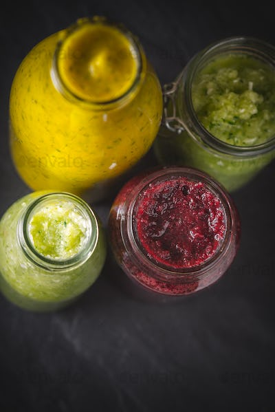 Bottles and jar with different smoothie on the dark stone table vertical