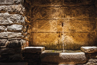 Small fountain in the stone wall