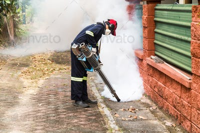 Worker fogging drain at residential area with insecticides to ki