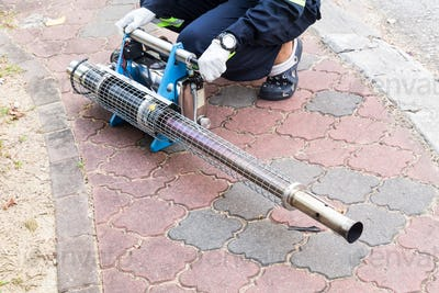 Worker preparing machine to fog with insecticides to kill aedes