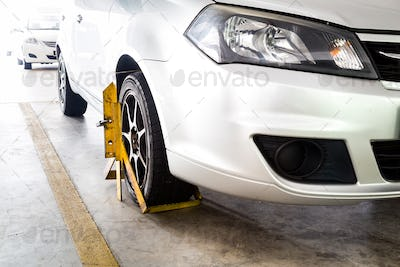 Car wheel clamped for illegal parking violation at car park