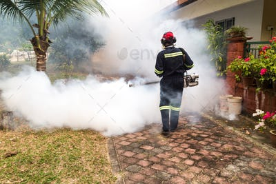 Worker fogging residential area with insecticides to kill aedes