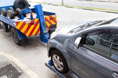 Tow truck towing a broken down car on the street