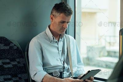 Man using a digital tablet on a bus