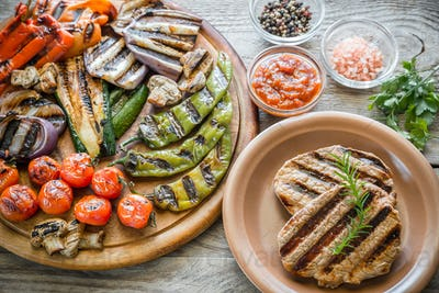 Grilled vegetables with beef steak on the wooden board