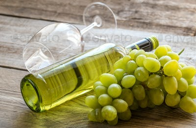Bottle of white wine with bunch of grape