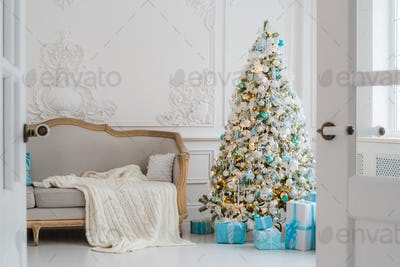 Stylish Christmas interior with an elegant sofa. Comfort home. Presents gifts underneath the tree in