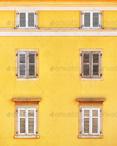 Building facade and old windows with classic wooden shutters bli