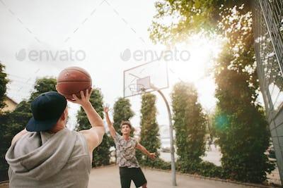 Streetball players on court playing basketball.