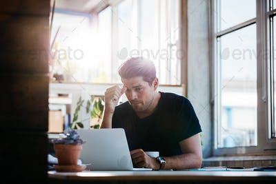 Business man thinking about a problem at his laptop