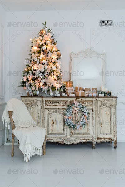 Christmas tree on wooden chest of drawers commode bureau in white interior, decorated with