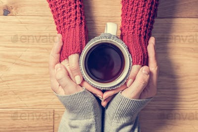 A couple in love warming hands with a hot mug of tea