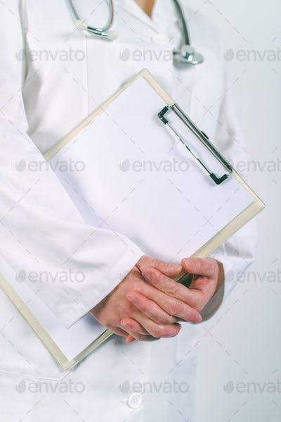 Female doctor in white uniform posing with blank clipboard pad