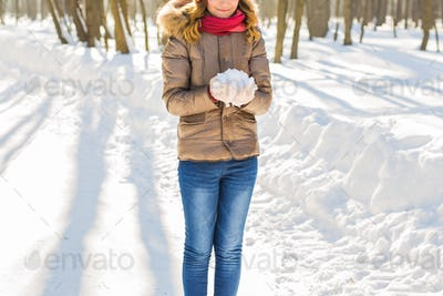 Young girl holding snow in mittens