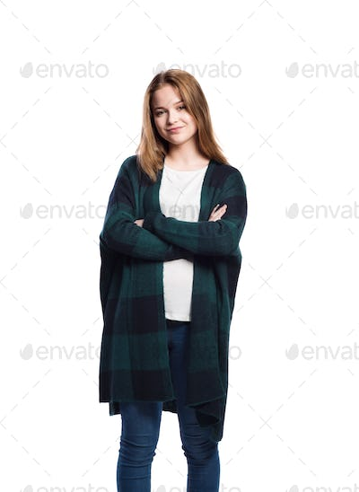 Girl in jeans and long sweater. Studio shot, isolated.
