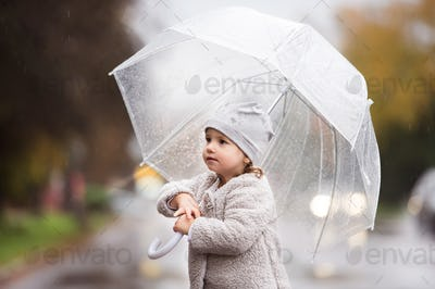 Little girl under the transparent umbrella outside, rainy day.