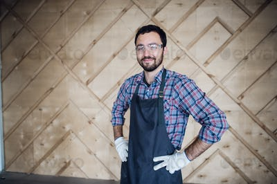 Young male carpenter wearing gloves and glasses with hands on hips