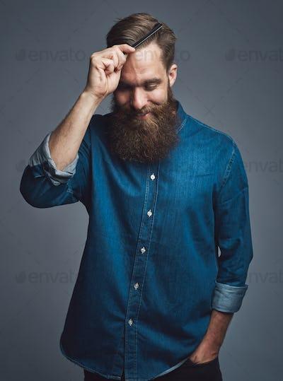 Cheerful man in beard combing his hair