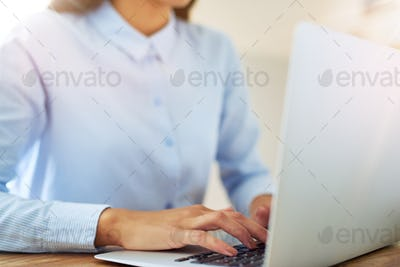 Young woman typing on a laptop computer