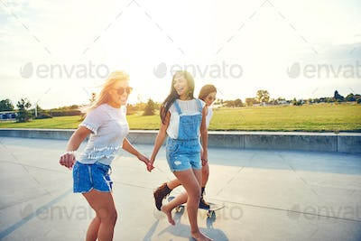 Three young friends skateboarding at sunrise