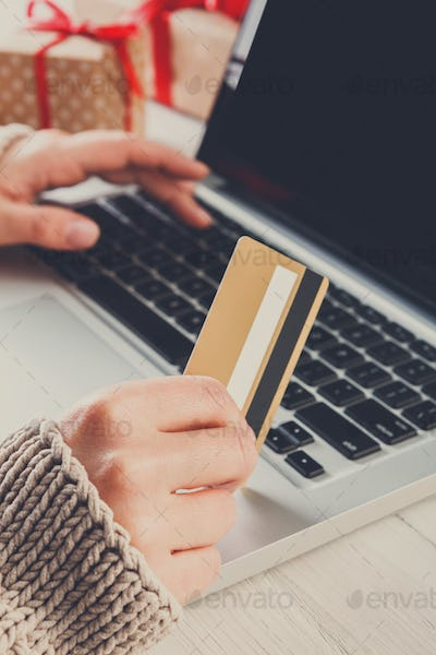 Woman christmas shopping online with a credit card