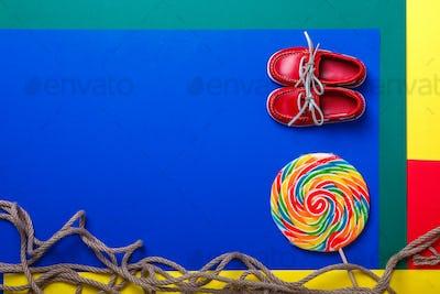 Small red boat shoes near big multi-colored lollipop