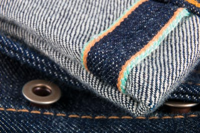 Close up of jeans fragment with button. Denim texture. Selvage.