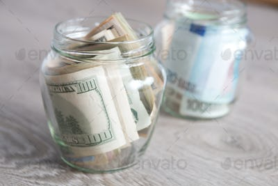 Money. Dollars and euro  in two open jars on grey wooden background.  Copy space.