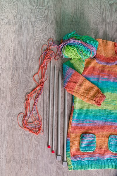 Knitting. Knitted sweater. Multicolor ball of yarn with needles near the handmade products