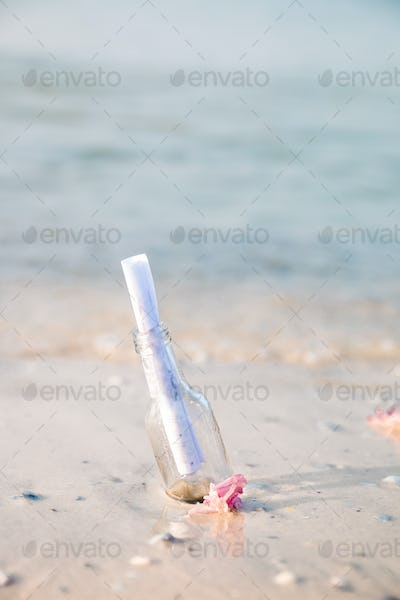 Bottle with a message or letter on the beach. SOS. Copy space. Help.