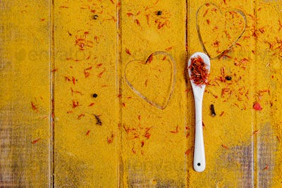 Heart of spices and seasonings. White spoon with saffron on curry background.