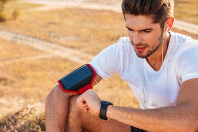 Concentrated young sportsman sitting and using smart watch