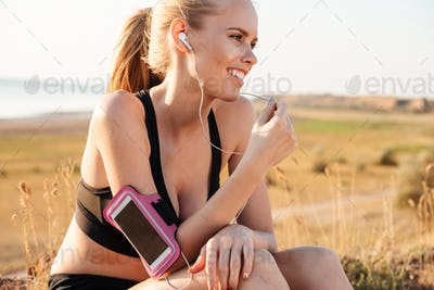 Woman runner listening to music with mobile phone in armband