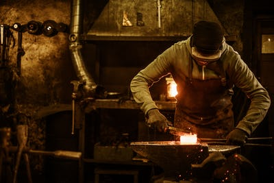 Blacksmith with brush handles the molten metal on the anvil in smithy
