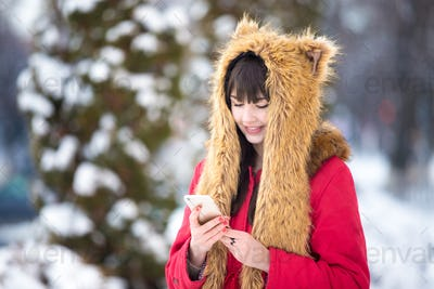 Woman outdoors with cellphone in wintertime