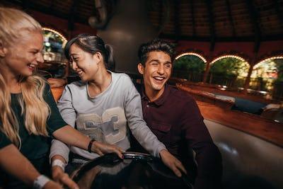 Enthusiastic people enjoying a ride at amusement park