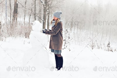 Woman making a snowman in winter time