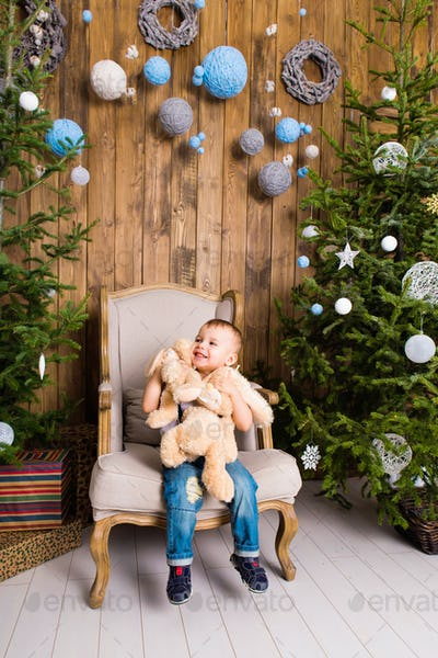 Little boy playing with toy at home near the Christmas tree.