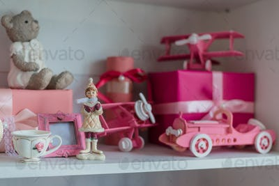 Christmas gifts in box on a shelf, pink car, airplane, wooden horse and gingle bell.