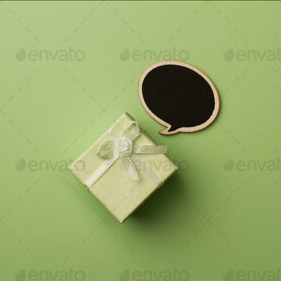 Concept little gift box with wooden speech bubble for messages